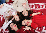 Smiling Happy girl friends group in New Year's sweater lying down on the floor  Having fun together at winter holiday time