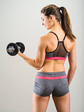 Sexy young woman doing dumbbell curl