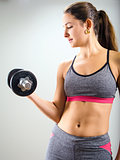 Young woman concentrating on dumbbell curl