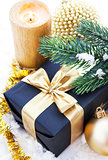 Golden Christmas composition with gift box, candle and branch of