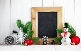Christmas still life with snowman and firtree on wooden board