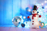 Christmas snowman with balls and garland on wooden board