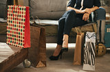 Close up on shopping bags and woman on couch in background
