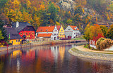 Autumnal landscape with coloured house over river