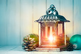 Christmas lamp with pinecone and ball on wooden board