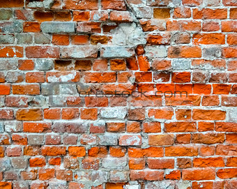 Brick damaged wall with cracks as background