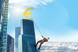 Businessman climbing skyscraper with euro sign