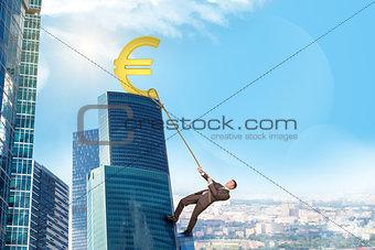 Businessman climbing skyscraper with euro sign