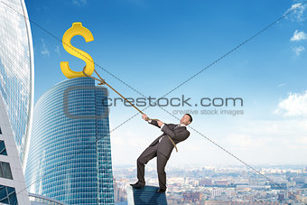 Businessman climbing skyscraper with dollar sign