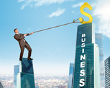 Businessman climbing skyscraper with word business