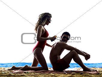 couple applying sun protection on the beach