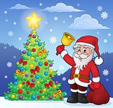 Santa Claus with bell by Christmas tree
