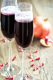 Two glasses of champagne with pomegranate seeds