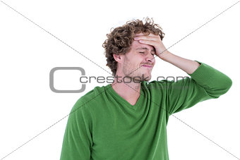 Anxious casual man standing with hand on forehead