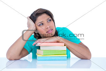 Thoughtful pretty brunette with hand on books