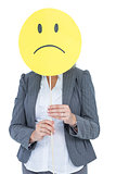 Businesswoman holding sad smiley face