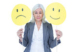 businesswoman holding a sad and a happy smiley