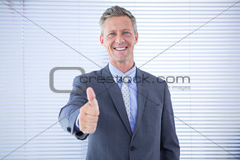 Smiling businessman giving thumbs up at the camera
