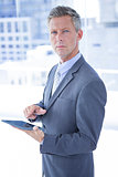 Businessman holding a tablet and looking at the camera