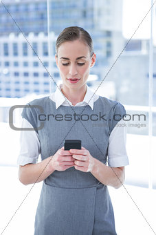 Smiling businessman texting with his mobile phone