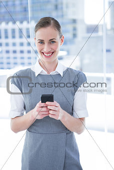 Smiling businessman texting with his mobile phowomen