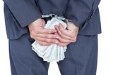 businessman in handcuffs holding bribe