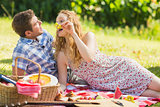 Young couple eating grapes at a picnic