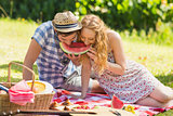 Young couple on a picnic eating watermelon