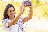 Pretty brunette taking a selfie with retro camera in the park