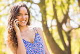Pretty brunette having phone call in the park