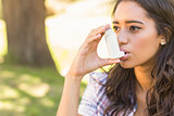 Pretty brunette using inhaler