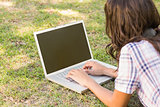 Pretty brunette lying in the grass and using laptop