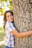 Pretty brunette hugging tree