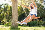 Pretty brunette swinging in park