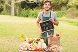 Handsome farmer standing at his stall and holding chalkboard
