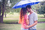 Cute couple hugging under the umbrella