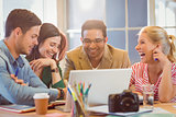 Happy creative business team using laptop in meeting