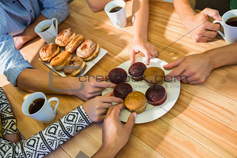 Business people taking cakes on table