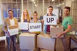 Creative business team holding cardboard written start up