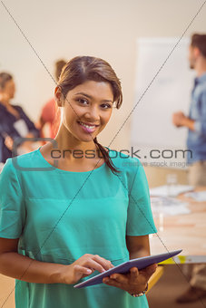 Casual businesswoman using tablet and looking at camera