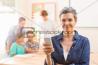 Casual businesswoman using her smartphone and smiling at camera