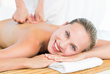 Pretty blonde enjoying a massage smiling at camera