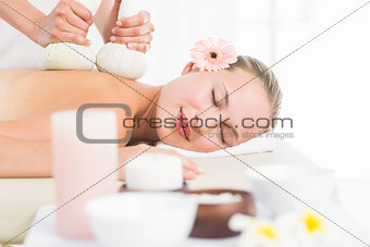 Beautiful blonde enjoying a herbal compress massage