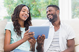 Happy couple using tablet together on the couch