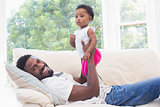 Happy father with baby girl on couch