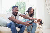 Happy couple on the couch playing video games