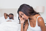 Upset woman sitting on edge of bed