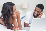 Relaxed couple using laptop on bed