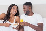 Relaxed couple in bed together eating cereal