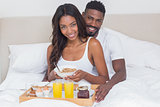 Relaxed couple having breakfast in bed together